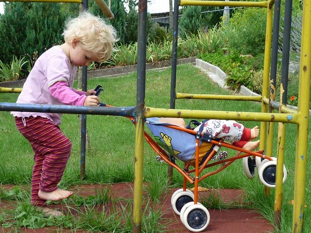 holčička co má golfky a hraje si s nimi venku, kdy vozí panenku